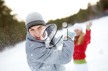 Image of attractive young man laughing during snowball play