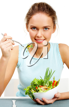 Portrait of pretty young girl with fork and bowl in hands eating vegetable salad