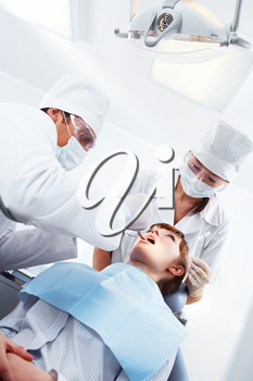 Image of patient sitting on dental armchair with doctor and nurse near by