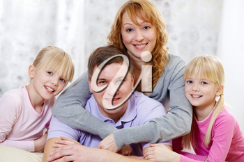 Portrait of wife hugging her husband with their daughters near by