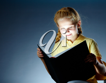Image of happy schoolgirl reading interesting book