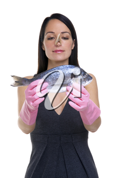 A woman wearing rubber gloves with a clothes peg on her nose holding a fish out in front of her, focus is on her face.