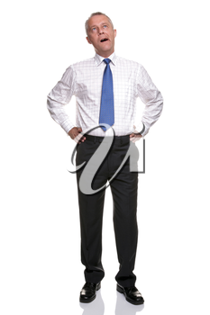 A mature businessman with his hands on his hips yawning, isolated on a white background.