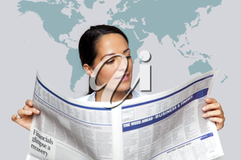 A businesswoman reading a financial newspaper with a map of the world on the wall behind her.