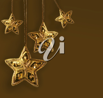 Royalty Free Photo of Gold Beaded Stars on a Brown Background