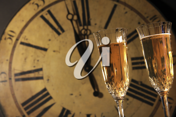 Royalty Free Photo of Champagne Glasses Against a Clock