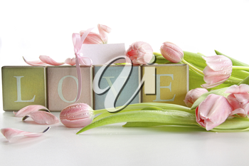 Royalty Free Photo of Coloured Blocks Saying Love With Pink Tulips