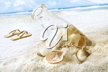 Royalty Free Photo of a Bottle of Seashells and Flip Flops on the Beach