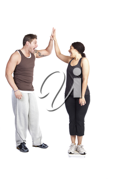 A happy woman standing on a weight scale celebrating with her personal trainer