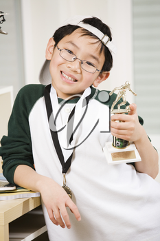 An asian boy showing his winning sport medal and trophy