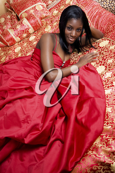 A beautiful black girl in a prom dress posing on a bed