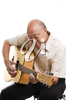 An isolated shot of a senior asian man playing guitar