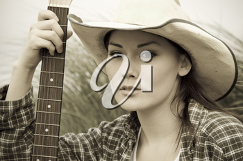 A portrait of a beautiful cowgirl with a guitar in sepia tone