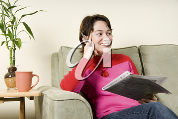 cute woman on couch looking at newspaper