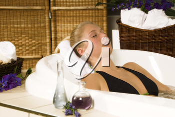 blond woman in a  spa bath relaxing with towels
