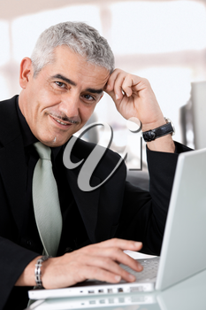 Gray haired creative director working on laptop computer at office, smiling.
