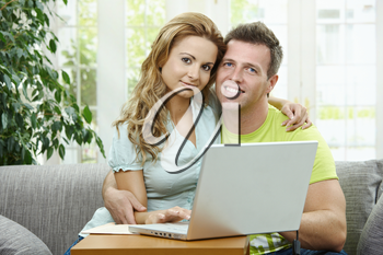 Couple using laptop computer at home together. Sitting on couch embracing,  looking at camera and smiling.