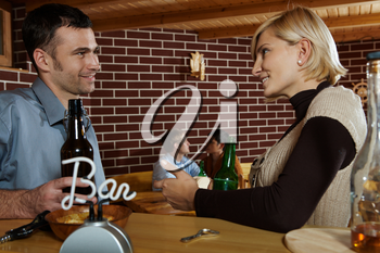 Man and woman chatting in bar, smiling at each other, young couple in background.
