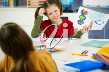 Portrait of elementary age schoolgirl showing colorful paining to classmate in art class in primary school classroom.