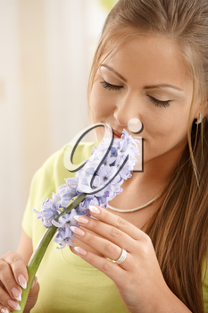 Beautiful woman smelling flowers with closed eyes, holding flower with two hands.