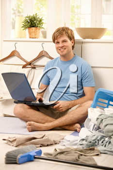 Lazy guy sitting with laptop computer instead of cleaning.