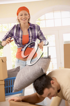 Smiling woman throwing pillow at boyfriend while moving house.