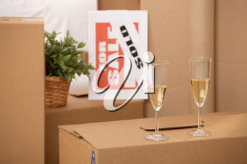 Celebration of new home, two champagne glasses standing on pile of boxes with for sale sign.