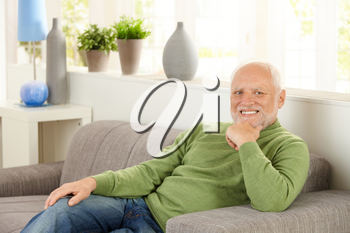 Portrait of pensioner sitting on couch at home, smiling.