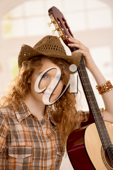 Attractive girl leaning on guitar, dressed in country style.