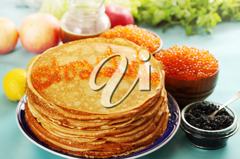 Ruddy pancakes with red and black caviar