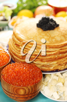 lot of red caviar in wooden plates with pancakes