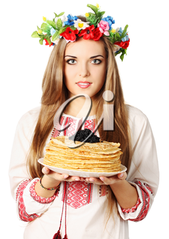 Ukrainian woman in a wreath holds pancakes with caviar