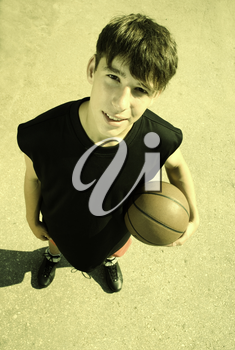 young adult with basketball, special toned photo f/x, focus point on face
