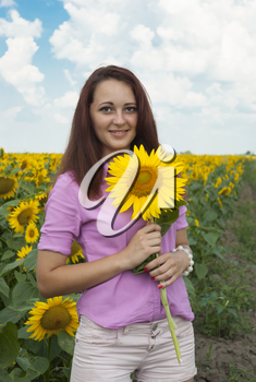 Royalty Free Photo of a Girl Holding a Sunflower