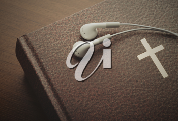 Holy Bible with a resting pair of earbuds over it. The word of God through hearing.