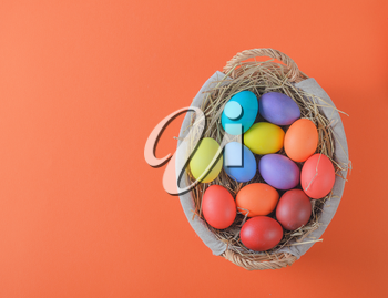 colorful easter eggs in a basket with hay on an orange background