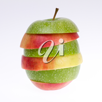 A sliced green and red apple isolated on a grey background