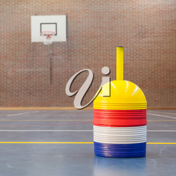 Interior of a gym at school, different colors of cones