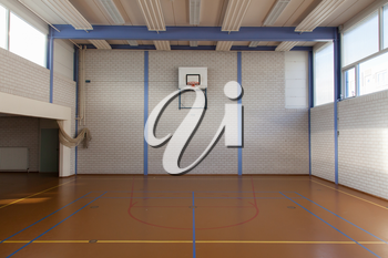 Interior of a gym at school, jumping high at the basket