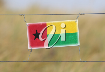 Border fence - Old plastic sign with a flag - Guinea Bissau