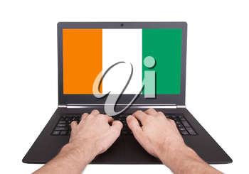 Hands working on laptop showing on the screen the flag of Ireland