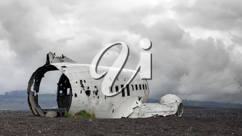 The abandoned wreck of a US military plane on Solheimasandur beach near Vik, Southern Iceland - Stormy clouds