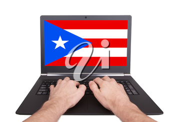 Hands working on laptop showing on the screen the flag of Puerto Rico
