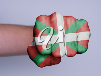 Very hairy knuckles from the fist of a man punching, flag of Basque Country