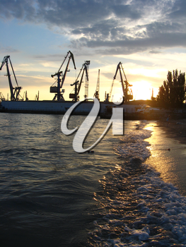 panorama of the everning sea with docks and hoisting crane