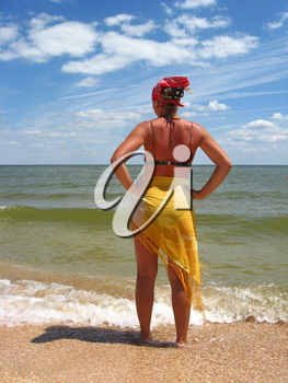 girl in bathing suit standing at the seacoast