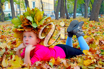 girl with a wreath of yellow leaves lying on the yellow leaves