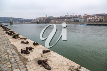 Shoes symbolizing the massacre of people shot at the river Danube in Budapest in a winter day
