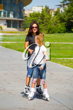Learning mother and daughter on roller skates in summer