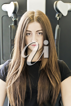 Vertical photo of brunette with long hair to train in gym